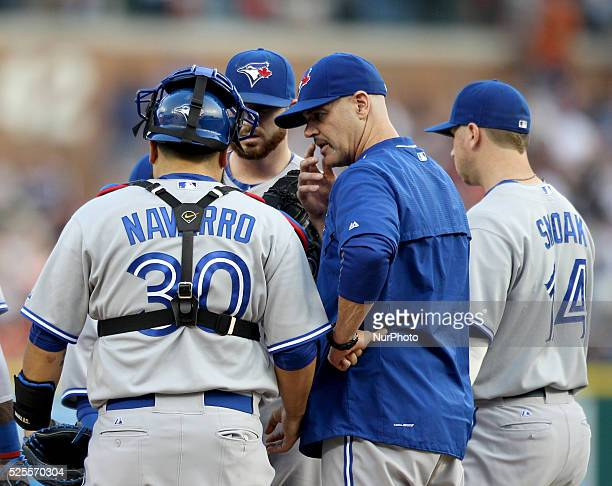 Toronto Blue Jays pitching coach Pete Walker talks to catcher Dioner Navarro and starting pitcher Drew Hutchison during the fourth inning of a...