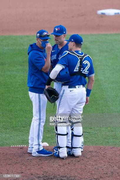 Toronto Blue Jays Pitching Coach Pete Walker talks with Toronto Blue Jays Pitcher Sean Reid-Foly and Toronto Blue Jays Catcher Reese McGuire during...
