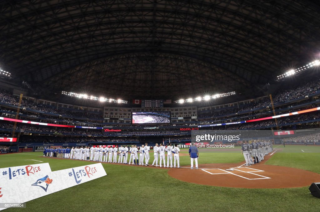Toronto Blue Jays players and Milwaukee Brewers players stand along the baselines during the playing of the anthems before the start of the home opener at Rogers Centre on April 11, 2017 in Toronto, Canada.