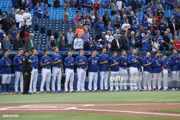 Toronto Blue Jays players stand in front of their dugout as they observe a moment of silence on the sixteenth anniversary of 9/11 before the start of...