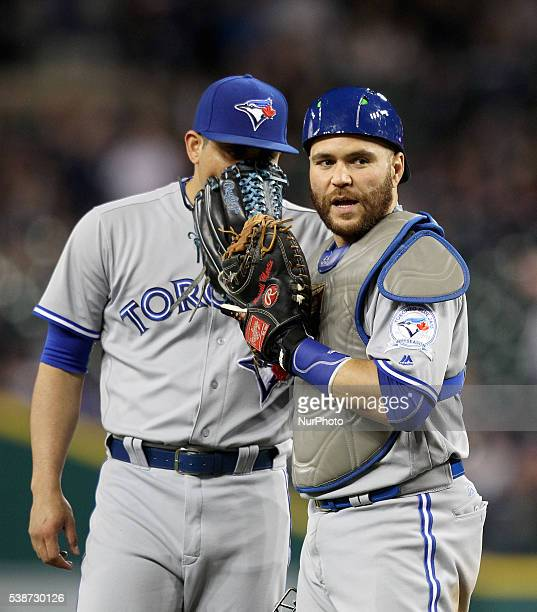 Toronto Blue Jays relief pitcher Roberto Osuna talks to catcher Russell Martin during the ninth inning of a baseball game against the Detroit Tigers...