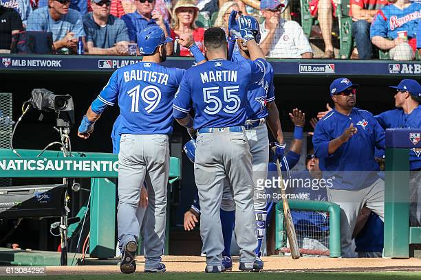 Toronto Blue Jays right fielder Jose Bautista and catcher Russell Martin are congratulated after scoring during game 1 of the ALDS between the...