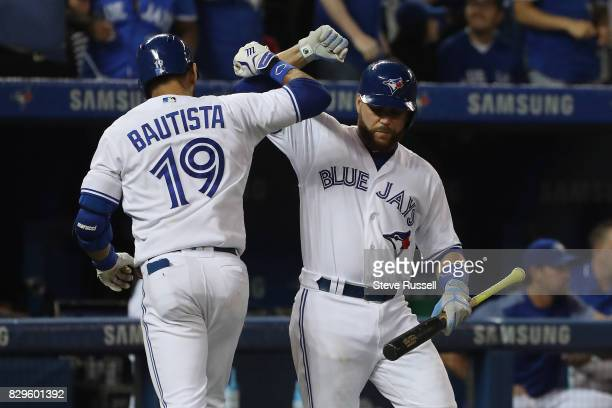 TORONTO ON AUGUST 10 Toronto Blue Jays right fielder Jose Bautista is congratulated by Russell Martin after hitting a seventh inning home run as the...