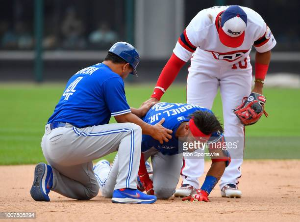 Toronto Blue Jays second baseman Lourdes Gurriel Jr grimaces while being assisted by Toronto Blue Jays third base coach Luis Rivera and Chicago White...