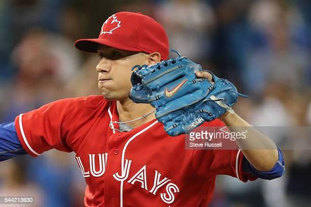 Toronto Blue Jays second baseman Ryan Goins wearing Marcus Stroman's glove pitches the 18th inning as the Toronto Blue Jays lose the Cleveland...