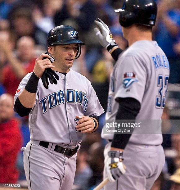Toronto Blue Jays shortstop Marco Scutaro is greeted by teammate Scott Rolen after scoring on a single by teammate Vernon Wells in the first inning...