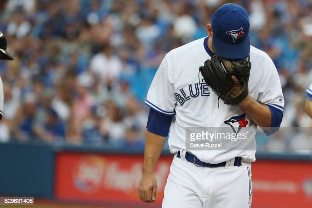 TORONTO ON AUGUST 10 Toronto Blue Jays starting pitcher Marco Estrada looks into his glove after the first inning as the Toronto Blue Jays shutout...