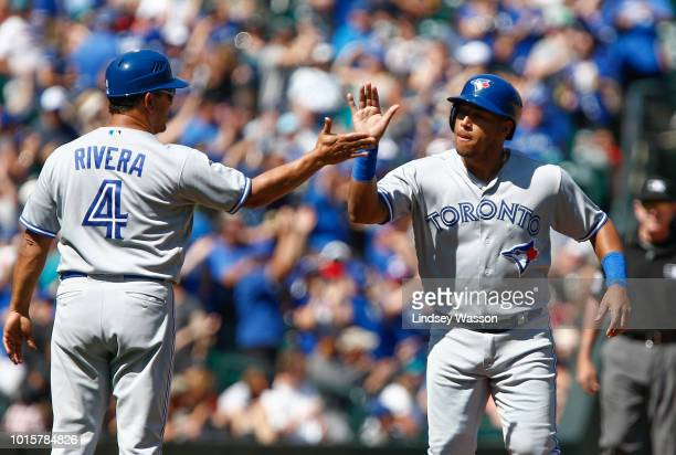 Toronto Blue Jays third base coach Luis Rivera congratulates Aledmys Diaz on his home run in the seventh inning against the Seattle Mariners at...