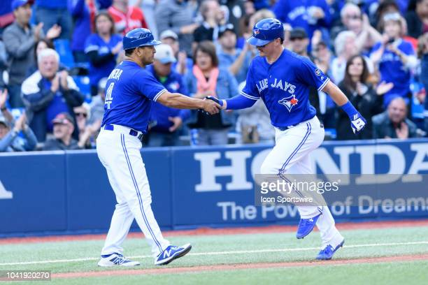 Toronto Blue Jays third base coach Luis Rivera congratulates Toronto Blue Jays Catcher Reese McGuire on his first career home run during the fifth...