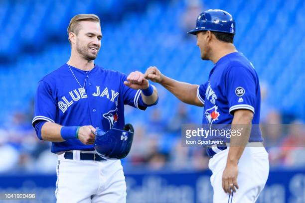 Toronto Blue Jays third base coach Luis Rivera congratulates Toronto Blue Jays Infield Jon Berti on his first MLB hit during the eighth inning of the...