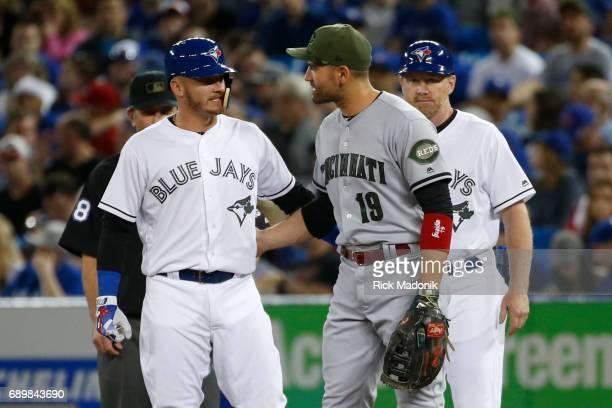 Toronto Blue Jays third baseman Josh Donaldson and Cincinnati Reds first baseman Joey Votto say hello after Donaldson reached 1st base Toronto Blue...