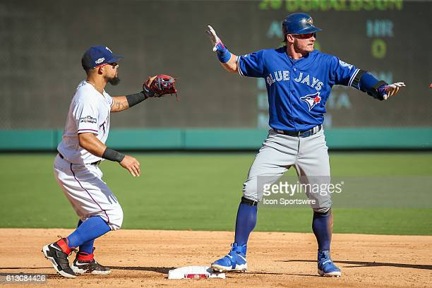 Toronto Blue Jays third baseman Josh Donaldson and Texas Rangers second baseman Rougned Odor both signal to the 2nd base umpire after a close play...