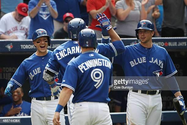 Toronto Canada August 29 Toronto Blue Jays shortstop Troy Tulowitzki left and first baseman Justin Smoak welcome back designated hitter Edwin...