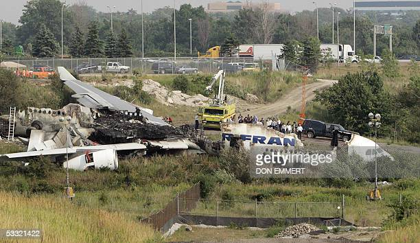 Officials view the wreckage of the Air France Airbus A340 at Toronto's Pearson International Airport 03 August 2005 one day after it skid off the...