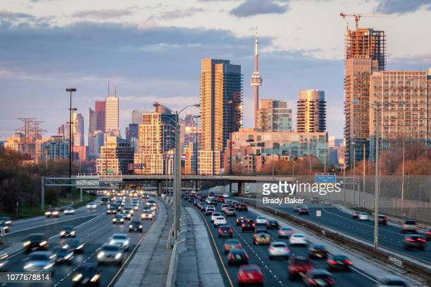toronto city skyline at sunset set beyond commuter traffic filling roadway - トロント ストックフォトと画像