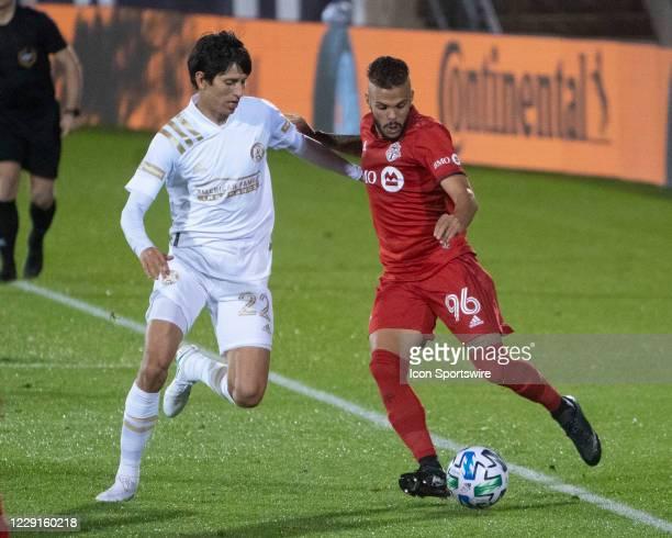 Toronto FC Defender Auro Jr passes the ball with Atlanta United FC Midfielder Jurgen Damm defending during the second half of a Major League Soccer...