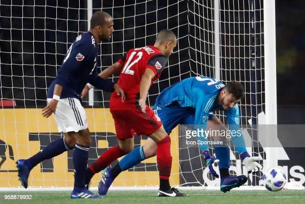 Toronto FC defender Jason Hernandez fends off New England Revolution midfielder Teal Bunbury as Toronto FC goalkeeper Alex Bono picks the ball up...