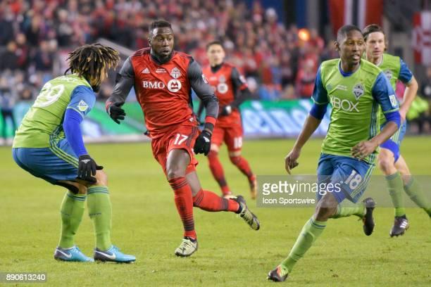 Toronto FC Forward Jozy Altidore trys to run past Seattle Sounders Defender Roman Torres as Seattle teammate Midfielder Marco Delgado keeps an eye on...