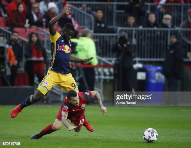 TORONTO ON NOVEMBER 5 Toronto FC forward Sebastian Giovinco falls as New York Red Bulls defender Kemar Lawrence leaps over him as Toronto FC play the...