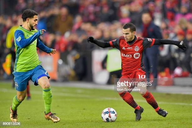 Toronto FC Forward Sebastian Giovinco is met by Seattle Sounders Midfielder Cristian Roldan during the MLS Cup Final played between the Seattle...