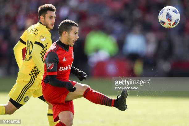 Toronto FC Forward Sebastian Giovinco kicks the ball as Columbus Crew SC Defender Milton Valenzuela looks on during the MLS regular season Toronto FC...