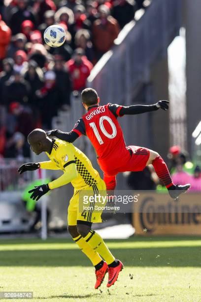 Toronto FC Forward Sebastian Giovinco leaps high to head the ball against Columbus Crew SC Defender Jonathan Mensah during the MLS regular season...