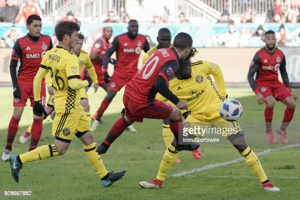 Toronto FC Forward Sebastian Giovinco leaps to kick the ball past Columbus Crew SC Defender Lalas Abubakar during the MLS regular season Toronto FC...