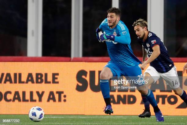 Toronto FC goalkeeper Alex Bono gets caught with the ball by New England Revolution midfielder Diego Fagundez during a match between the New England...