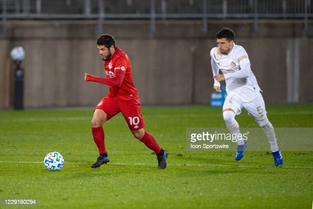 Toronto FC Midfielder Alejandro Pozuelo dribbles the ball up the field with Atlanta United FC Midfielder Eric Remedi in pursuit during the second...