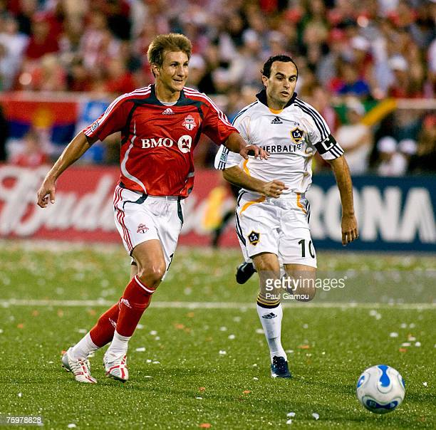 Toronto FC midfielder Chris Pozniak chases the ball with L.A. Galaxy forward Landon Donovan in pursuit at BMO Field in Toronto, Ontario, Canada on...