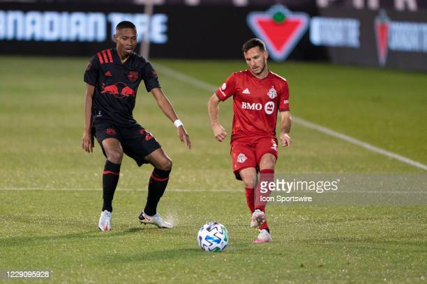 Toronto FC Midfielder / Forward Pablo Piatti passes the ball up the field with New York Red Bulls Defender Jason Pendant defending during the first...