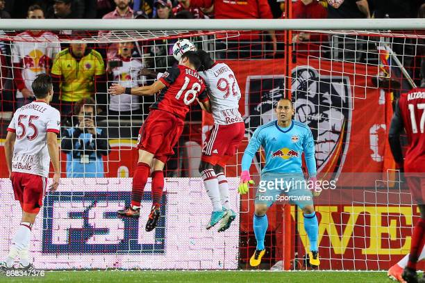 Toronto FC midfielder Marco Delgado battles New York Red Bulls defender Kemar Lawrence for a headball during the first half of the MLS Cup Playoff...