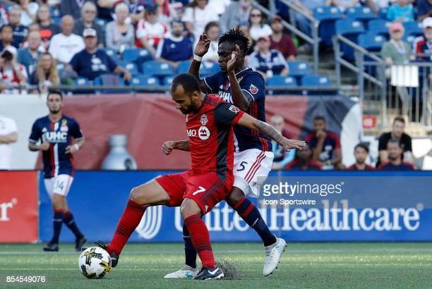 Toronto FC midfielder Victor Vazquez shields off New England Revolution midfielder Gershon Koffie during a match between the New England Revolution...