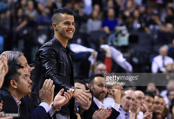 Toronto FC soccer player Sebastian Giovinco smiles from his courtside seat during the first half of an NBA game between the Atlanta Hawks and the...