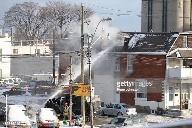TORONTO ON JANUARY 29 Toronto Fire shoot water from a hose into a top floor window to blast a mattress away from the opening A man is taken into...