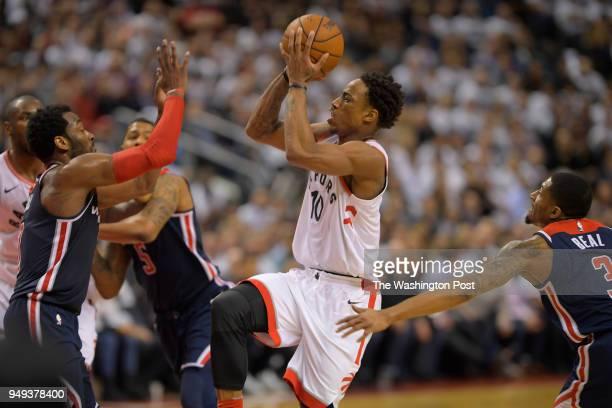 Toronto guard DeMar DeRozan center splits the defense of Washington guard John Wall left and Washington guard Bradley Beal right for a 4th quarter...