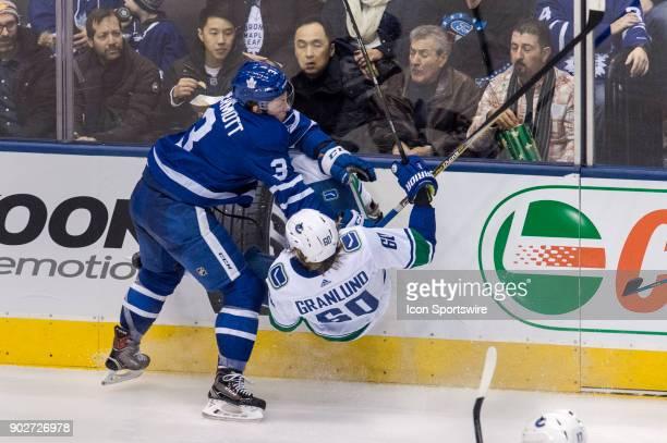 Toronto Maple Leaf Defenceman Travis Dermott checks Vancouver Canucks Winger Markus Granlund during the regular season NHL game between the Vancouver...