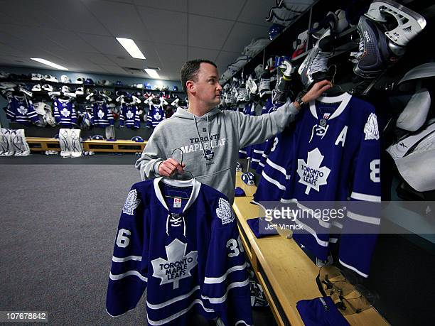 Toronto Maple Leafs assistant athletic therapist Marty Dudgeon hangs the jersey of Leafs player Mike Komisarek in the locker room before their game...