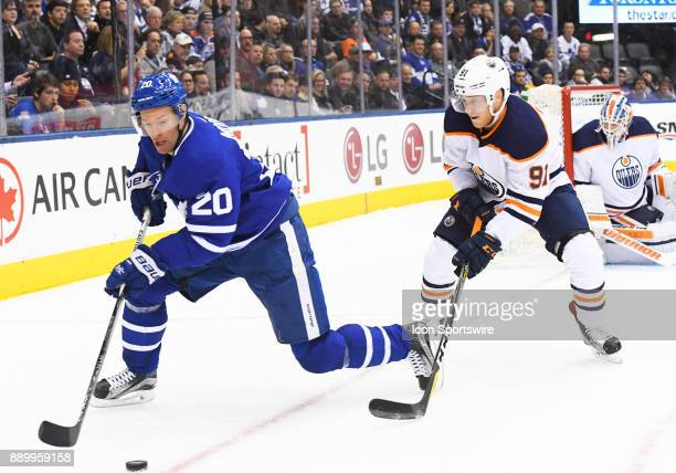Toronto Maple Leafs center Dominic Moore battles for a puck with Edmonton Oilers left wing Drake Caggiula during the first period in a game between...