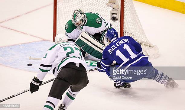 Toronto Maple Leafs center Jay McClement carves for the front of the net and goalie Kari Lehtonen followed by Dallas Stars defenseman Kevin Connauton...