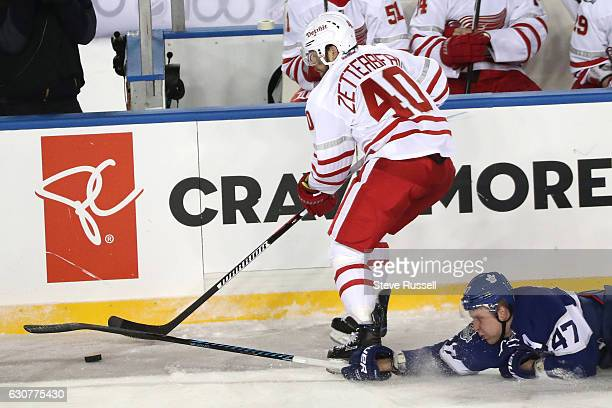 TORONTO ON JANUARY 1 Toronto Maple Leafs center Leo Komarov knocks the puck off of Detroit Red Wings left wing Henrik Zetterberg's stick as the...