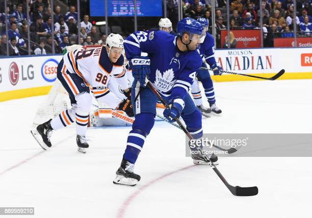 Toronto Maple Leafs center Nazem Kadri battles for a puck with Edmonton Oilers right wing Jesse Puljujarvi during the third period in a game between...