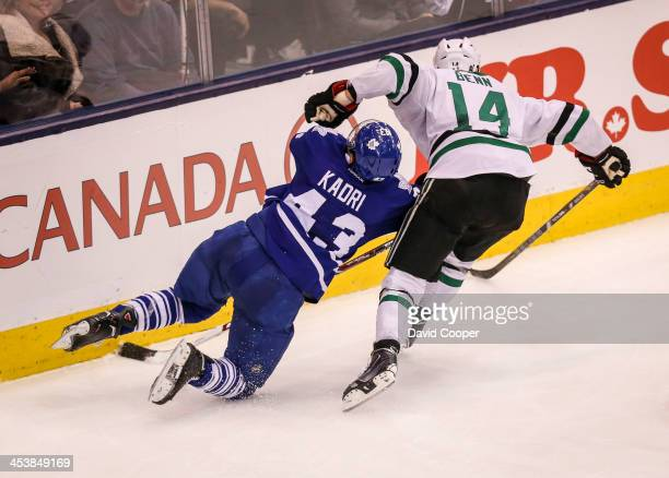 Toronto Maple Leafs center Nazem Kadri get knocked down tby Dallas Stars left wing Jamie Benn as they chase down the puck behind the Stars net during...