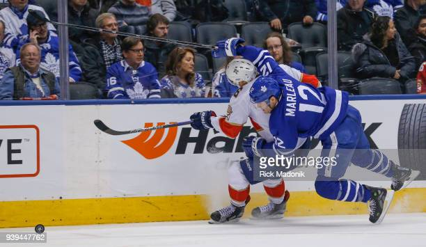 Toronto Maple Leafs center Patrick Marleau and Florida Panthers center Aleksander Barkov get tangled up chasing the puck down the boards Toronto...