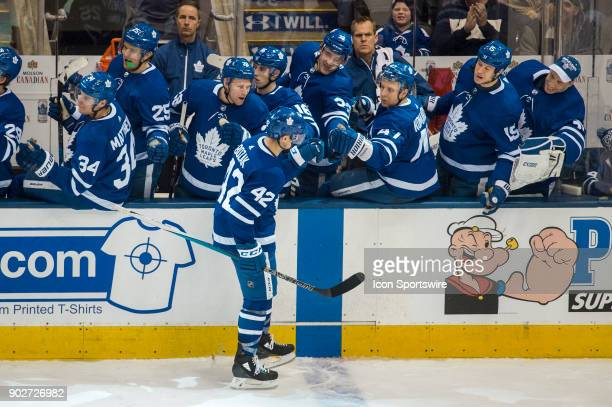 Toronto Maple Leafs Center Tyler Bozak is congratulated by teammates on the bench after scoring during the regular season NHL game between the...