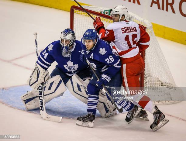 TORONTO ON SEPTEMBER 28 Toronto Maple Leafs defenseman JohnMichael Liles tries to clear Detroit Red Wings center Riley Sheahan from in front of...