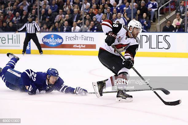 Toronto Maple Leafs defenseman Nikita Zaitsev makes a last second dive to try to knock the puck away from Jordan Martinook as the Toronto Maple Leafs...