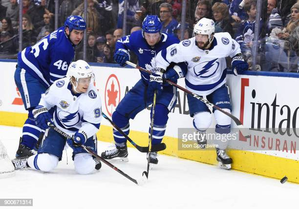 Toronto Maple Leafs defenseman Roman Polak and Toronto Maple Leafs defenseman Morgan Rielly battle for a puck with Tampa Bay Lightning right wing...
