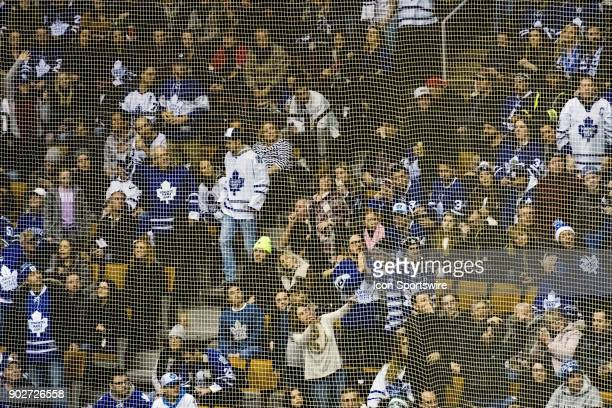 Toronto Maple Leafs fans as seen through the protective mesh behind the net during a break in action in the regular season NHL game between the...