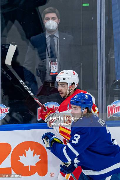 Toronto Maple Leafs General manager Kyle Dubas watches on as Toronto Maple Leafs Defenceman Justin Holl checks Calgary Flames Johnny Gaudreau into...